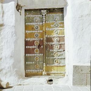 Old polychrome door set in whitewashed walls by Werner Forman