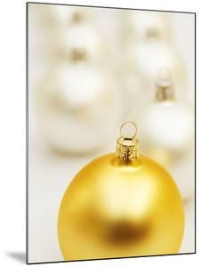 White Christmas tree decorations and a yellow one