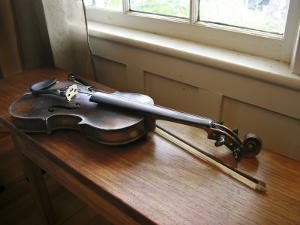 Antique Fiddle and Bow on Wooden Bench in Warm Sunlight from a Window by White & Petteway