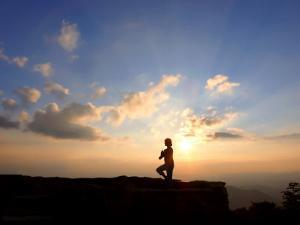 Woman Strikes the Yoga Tree Pose on Top of a Mountain at Sunset by White & Petteway