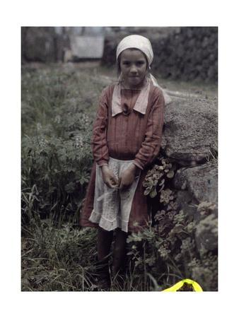 A Young Girl from a Farm Community Poses, Leaning Against a Rock
