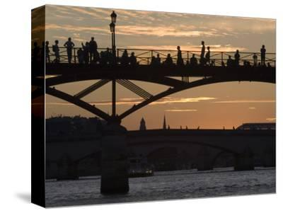 People Silhouetted on Footbridge over River Seine at Sunset
