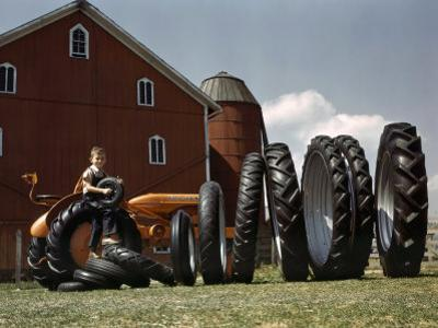 Boy Poses with Huge Rubber Tractor Tires by Willard Culver