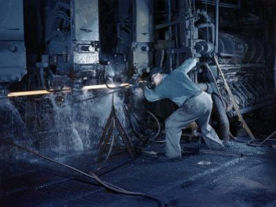 Man Operates a Machine Rolling Flat Sheets of Steel into Pipes by Willard Culver