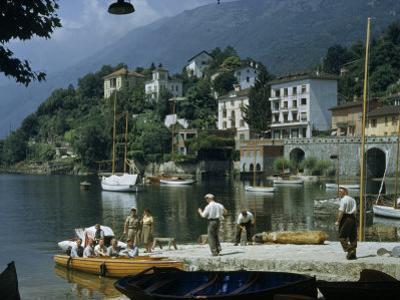 People Gather on Dock Below Summer Villas Overlooking Lake by Willard Culver