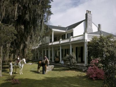 People in Period Costumes Sit on Horses on Lawn of Plantation House by Willard Culver