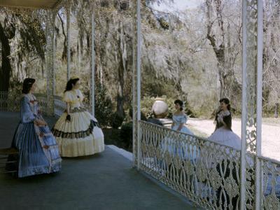 Women Stand on Antebellum Mansion's Porch Framed by Belgian Ironwork by Willard Culver