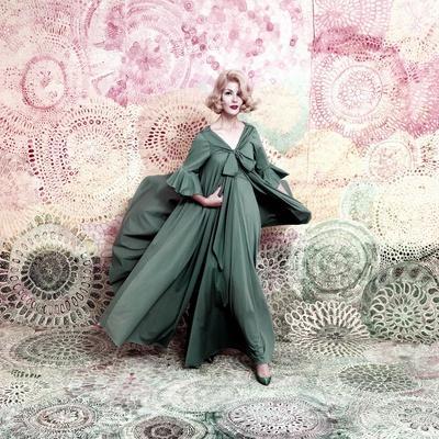 Pose Against a Mural of Swirling Roses, Model Wearing Blue Float of Peignoir in Blue Nylon Yarn