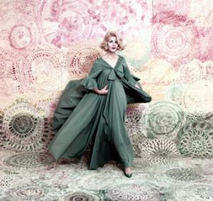 Pose Against a Mural of Swirling Roses, Model Wearing Blue Float of Peignoir in Blue Nylon Yarn by William Bell