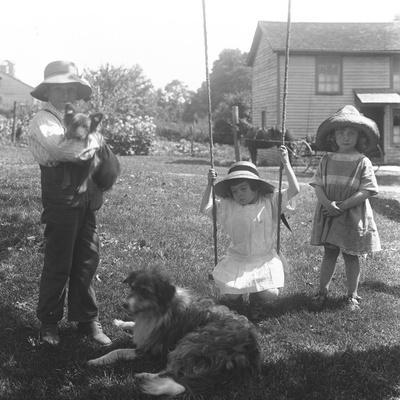 Children with a Dog and Puppy Gathered around a Rope Swing at the Mccready Farm