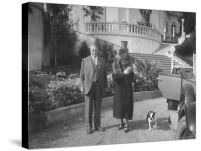 William Randolph Hearst and Mrs. Burton Holmes at San Simeon Estate with Boston Bull Terrier