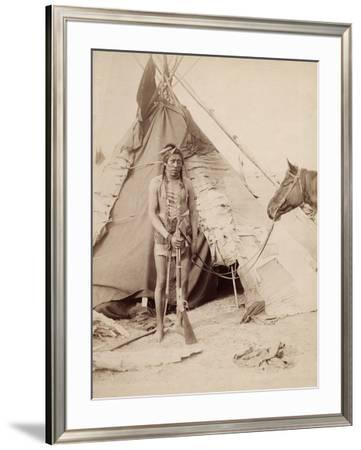A Native American Stands at the Entrance to His Teepee Holding a Rifle, 1880-90 by William Notman