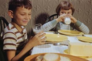 Children Drinking Milk at Dinner Table by William P. Gottlieb