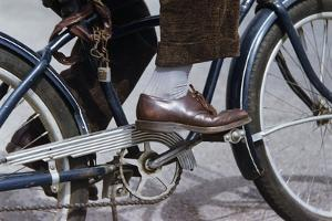 Man Riding Bicycle in Dress Shoes by William P. Gottlieb