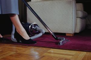 Woman Vacuuming Rug by William P. Gottlieb