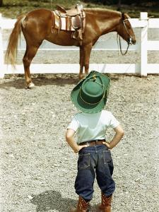 Young Cowboy Looking at Horse by William P^ Gottlieb