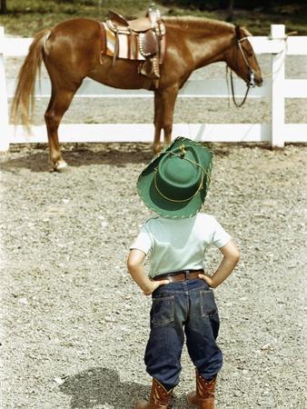 Young Cowboy Looking at Horse