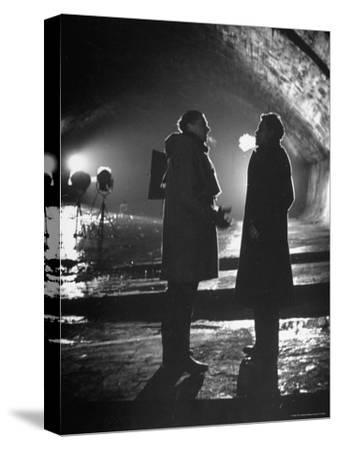 """Carol Reed Coaching Orson Welles as They Stand Against Floodlights During Filming """"The Third Man."""""""
