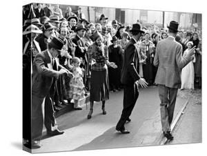 Men dancing in the street as revelers celebrate New Orleans Mardi Gras. February 1938 by William Vandivert