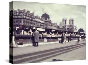 People Shopping at Book and Print Stalls Along the Seine River by William Vandivert