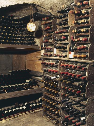 Wine Bottles on a Rack in a Wine Cellar-G^ Cigolini-Photographic Print