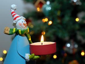 Close-Up of a Snow Man Candle in Front of a Tree with Christmas Lights by Winfred Evers