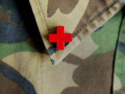 Red Cross on the Collar of a Camouflage Jacket
