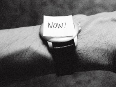 The Word Now as a Reminder Attached to a Watch on a Male Arm by Winfred Evers