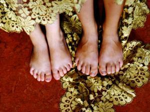 Two Pair of Feet of Small Children with Textile Spread around Them by Winfred Evers