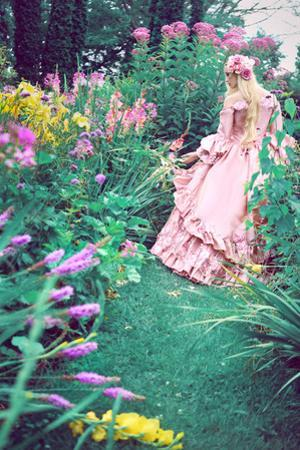 A Beautiful Princess with Long Blond Hair Wanders Through a Garden of Pretty Flowers