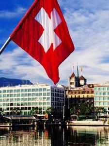 Swiss Flag on Mont Blanc Bridge with Quai General Guisan in Background, Geneva, Switzerland by Witold Skrypczak