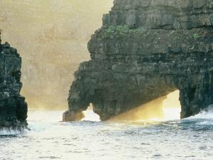 Sunlight Beaming Through Arches in Surf-Pounded Rock Formations by Wolcott Henry