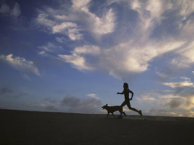 Woman and Her Dog Run Along the Beach with Beautiful Sky-Skip Brown-Photographic Print
