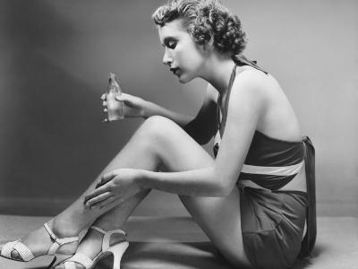 Woman Applying Cosmetic on Calf-George Marks-Photographic Print