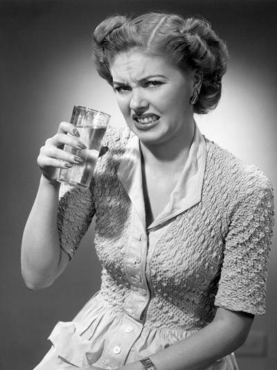 Woman Drinking Glass of Water With Look of Disgust-George Marks-Photographic Print