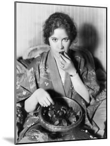 Woman Eating Chocolates Out of a Bowl