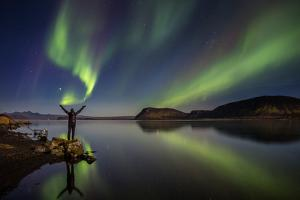Woman Enjoying the View of the Northern Lights, at Lake Thingvellir, Iceland