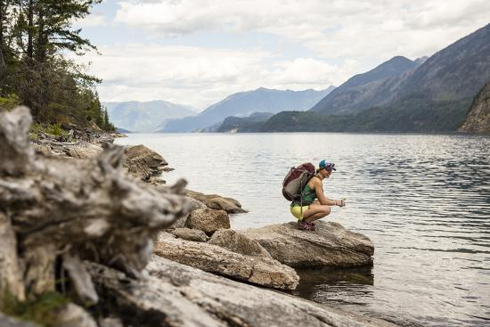 Woman Hangs Out On The Shore Of A Lake In British Columbia In Valhalla National Park, Bc-Hannah Dewey-Photographic Print