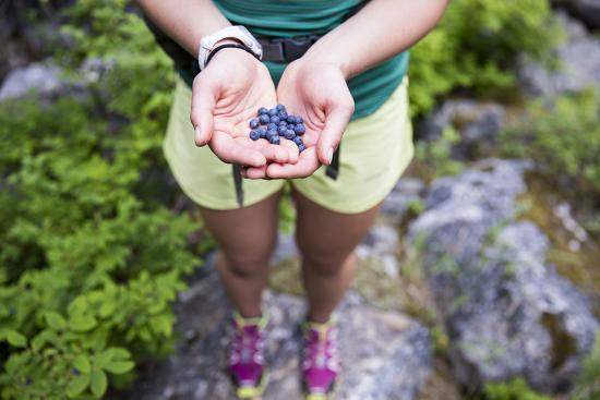 Woman Holds Out Wild Huckleberries She Picked While Hiking-Hannah Dewey-Photographic Print