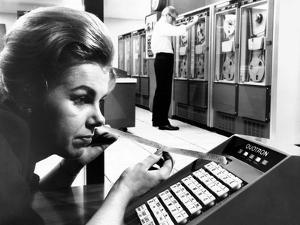 Woman Holds Tape with the Latest Stock Prices Printed by the Quotron II