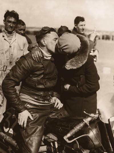 Woman Kissing Motorcycle Racer--Photographic Print