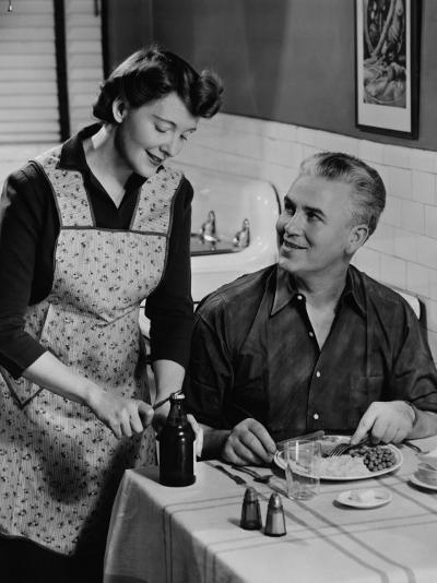 Woman Opening Beer Bottle For Man Eating Dinner-George Marks-Photographic Print
