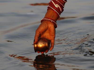 Woman Praying on the Banks of the River Ganges Fills Water into a Copper Vessel for a Ritual--Photographic Print
