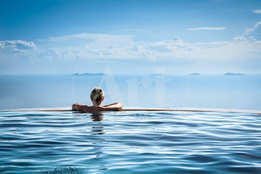Woman Relaxing in Infinity Swimming Pool on Vacation Photographic Print by  Splendens | Art.com