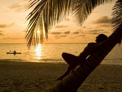 Woman Resting on a Palm Tree at Sunset, Sunset over the Caribbean Sea-Richard Nowitz-Photographic Print