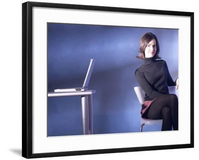Woman Sitting Beside Table with Laptop--Framed Photographic Print