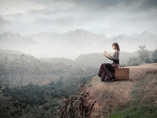 Woman Sitting On A Suitcase And Reading A Book With Landscape On The Background-olly2-Art Print