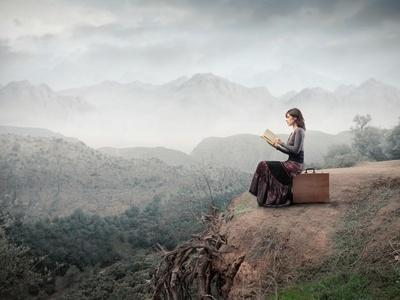 https://imgc.artprintimages.com/img/print/woman-sitting-on-a-suitcase-and-reading-a-book-with-landscape-on-the-background_u-l-pn0cv60.jpg?p=0
