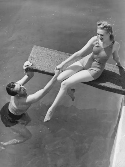 Woman Sitting on Diving Board, Man Grasping Her Hand-George Marks-Photographic Print