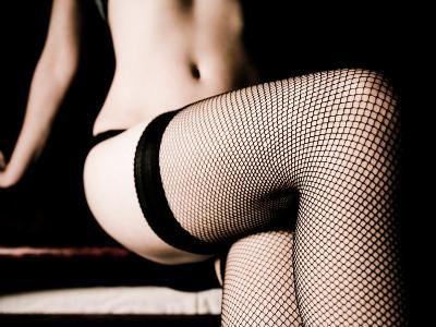 Woman Sitting on Edge of Bed and Wearing Lingerie with Fishnet Stockings--Photographic Print